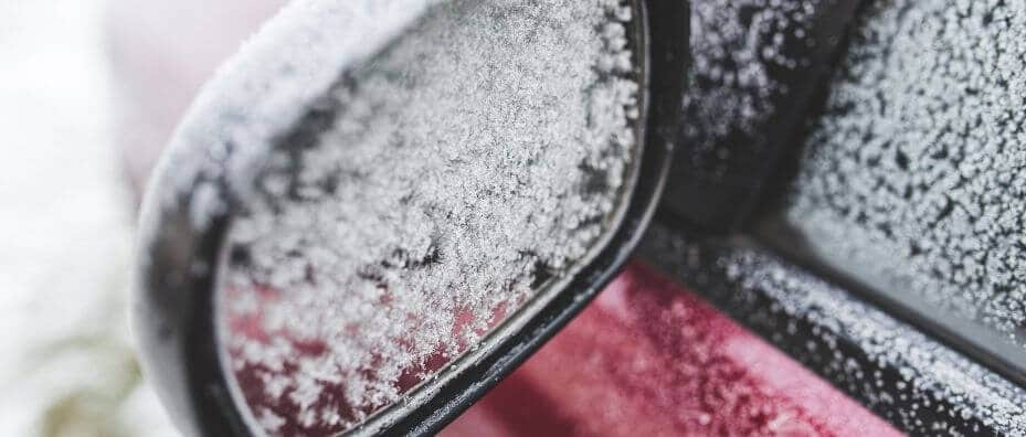 car rear view mirror covered in snow